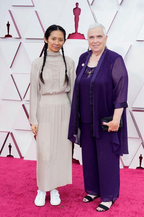 Đạo diễn Chloe Zhao (trái) khác lạ với mái tóc tết hai bên, cô đi cùng Charlene Swankie trên thảm đỏ. Chloe Zhao được kỳ vọng sẽ làm nên lịch sử trở thành là người phụ nữ đầu tiên nhận bốn giải thưởng về biên tập, viết kịch bản, đạo diễn và sản xuất thông qua tác phẩm Nomadland.