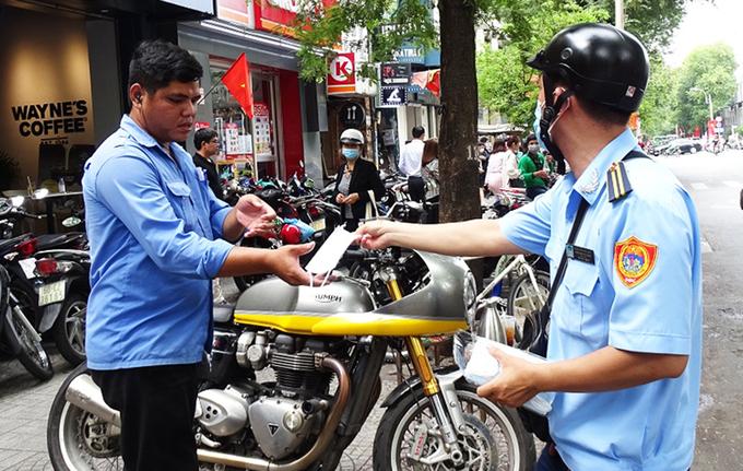 Người dân ở phường Bến Nghé, quận 1 được phát khẩu trang miễn phí - Ảnh: VNE
