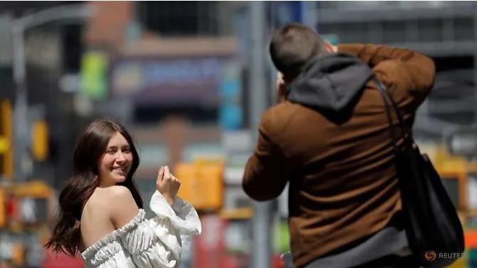 Một người chụp ảnh ở Quảng trường Thời đại sau khi Trung tâm Kiểm soát và Phòng ngừa Dịch bệnh (CDC) công bố hướng dẫn mới về việc đeo khẩu trang ngoài trời