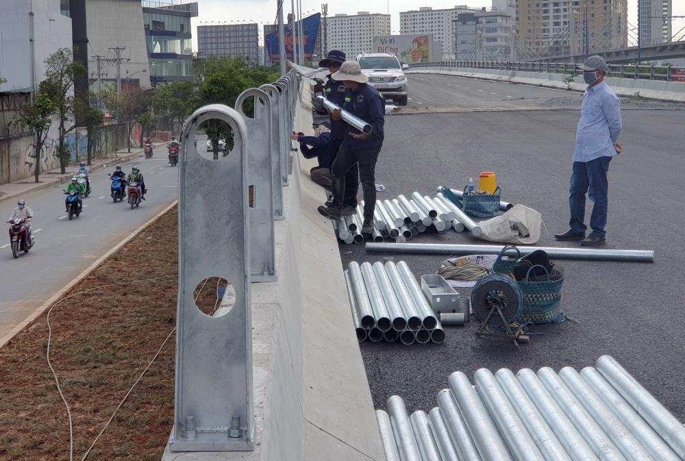 Các công nhân cũng đang hối hả lắp lan can, đấu nối hệ thống đèn chiếu sáng cũng như kẻ vạch phân làn