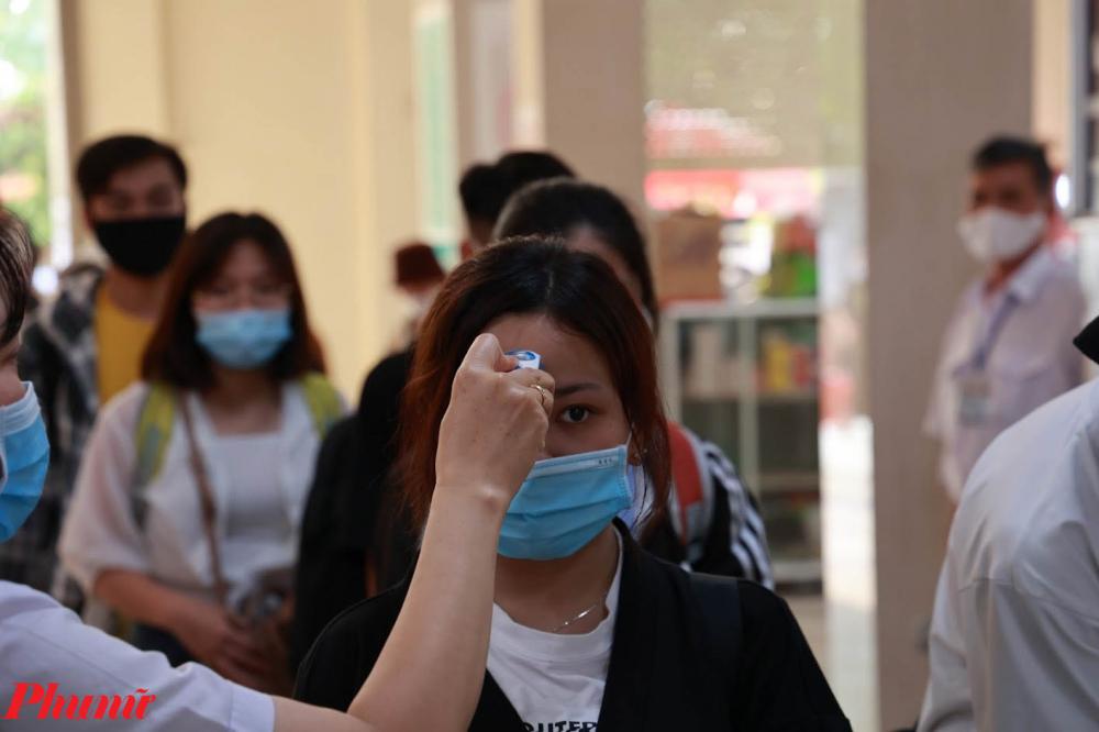 Người dân được kiểm tra thân nhiệt và rửa tay sát khuẩn trước khi mua vé.