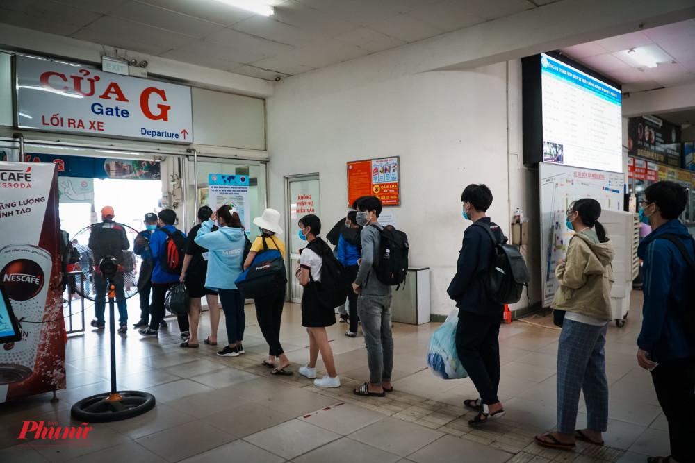 Để ra xe, hành khách phải xếp hàng kiểm soát vé và đo thân nhiệt