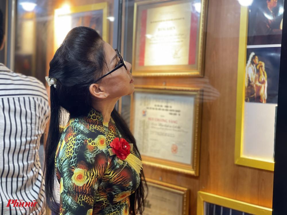 NS ƯT Phượng Loan nhìn lại những bức ảnh của các tiền bối được trưng bày trong những khung kính.