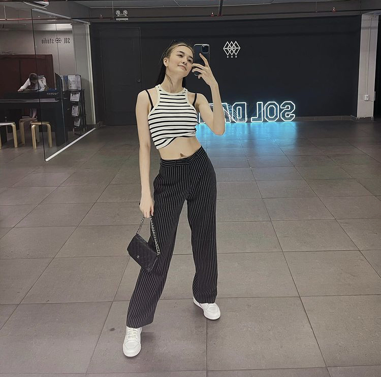 Khác với cô em gái, Thiều Bảo Trang chọn croptop khoét vai để lộ cả dây bra nhưng cũng tạo nên phong cách mới lạ khi kết hợp cùng quần ống suông và sneaker khỏe khoắn.