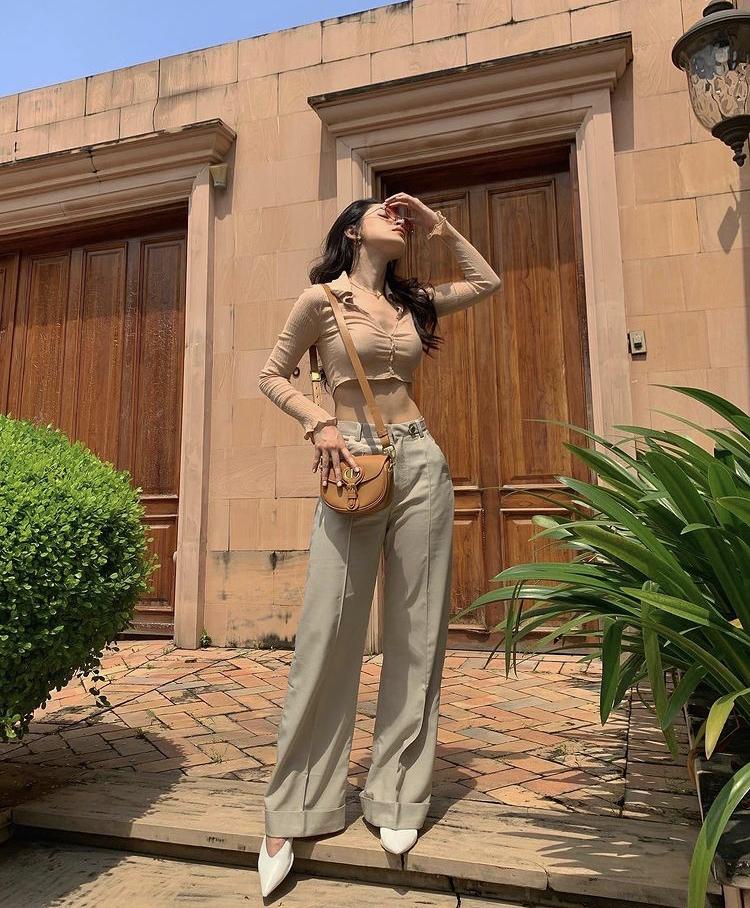 Chi Pu chọn áo croptop kiểu dáng cardigan mix cùng quần suông với sắc màu nhã nhặn rất hợp cho không khí mùa hè. Người đẹp không quên thêm phụ kiện mắt kính, túi xách mini để hoàn thiện tổng thể trang phục.