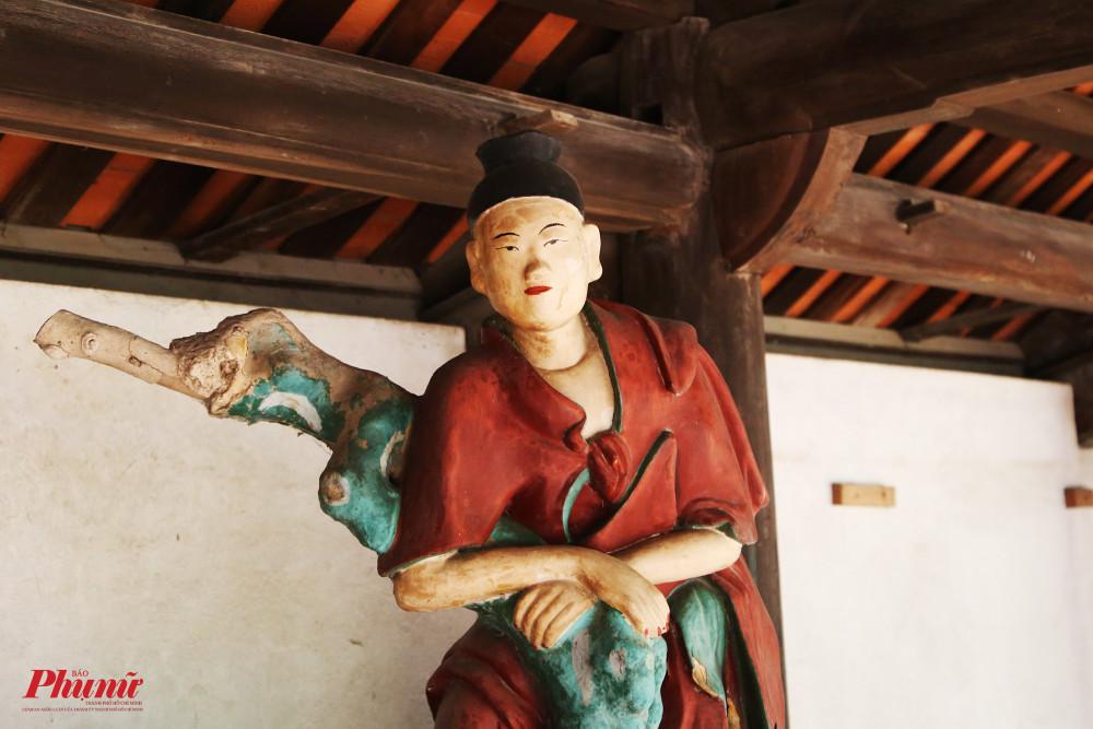 Cận cảnh một bức tượng La Hán trong chùa. Du khách cũng có thể nhìn thấy hệ thống kèo, cột gỗ rất to kiến tạo nên các gian của chùa.