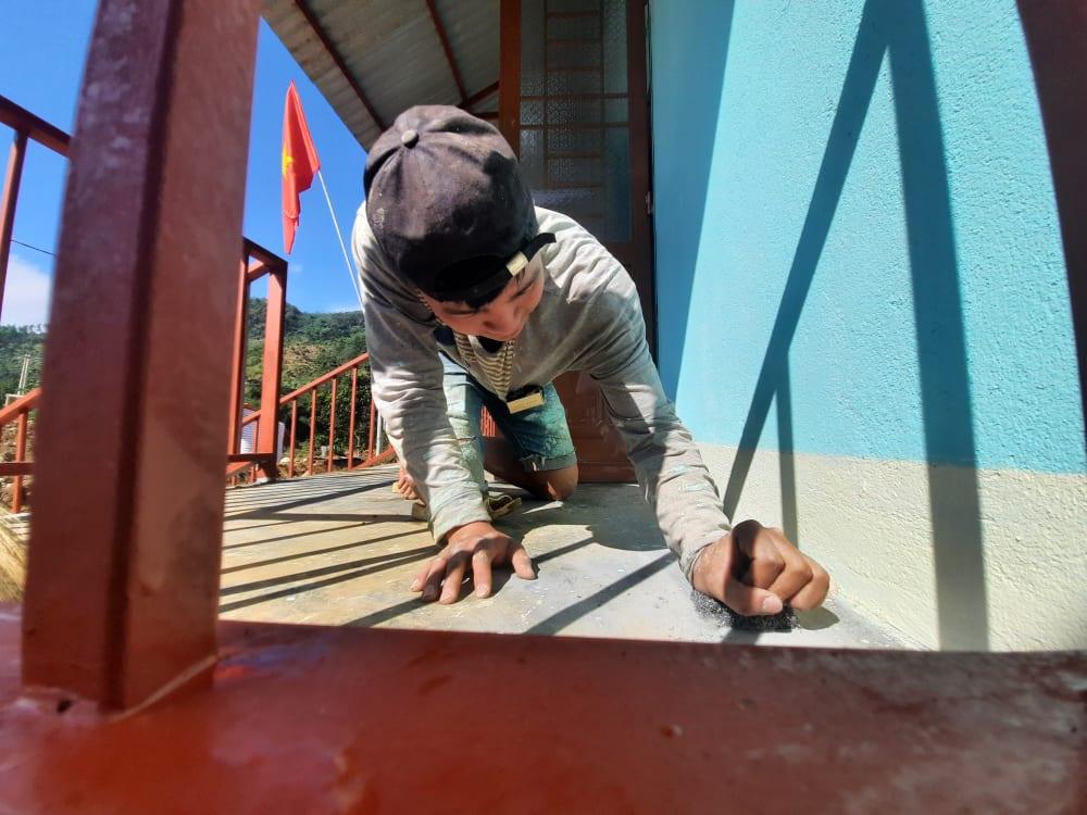 Tranh thủ giúp ba mẹ chà những vết sơn còn vương trên nền nhà mới