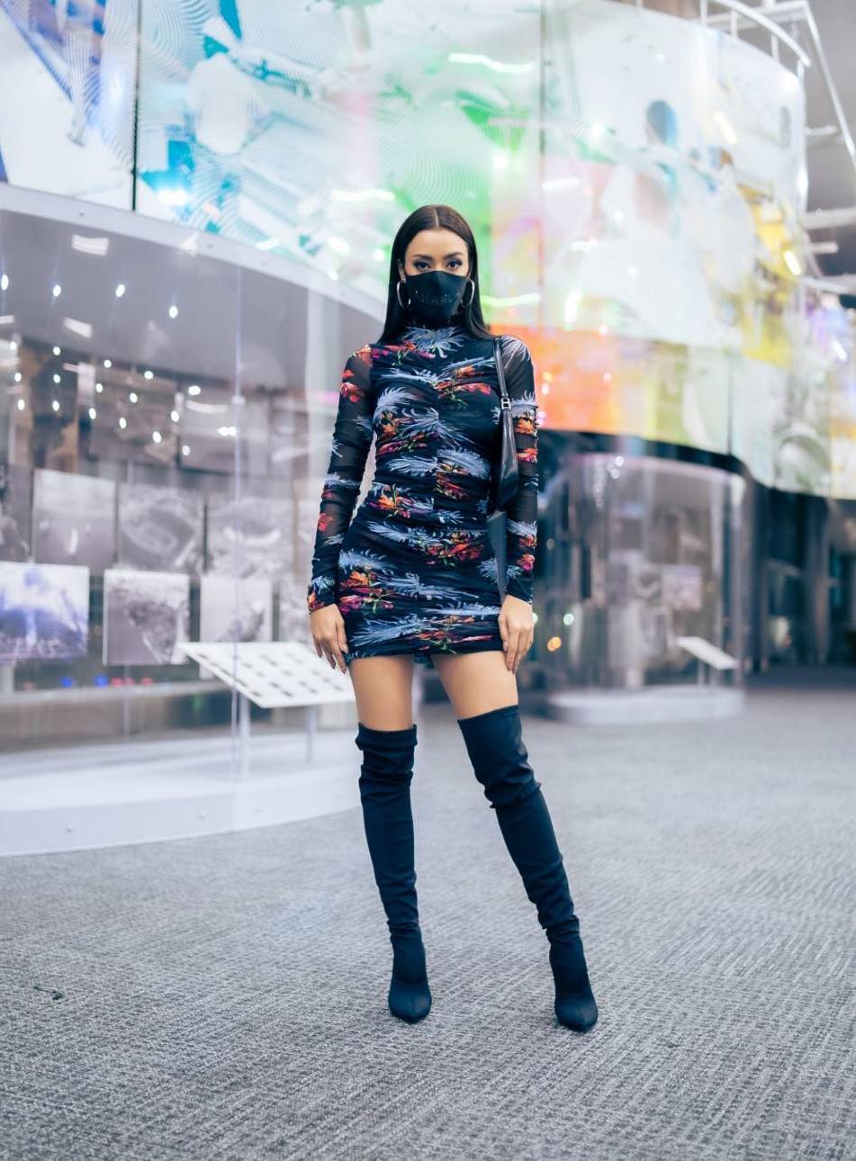 Khi đến Mỹ, người đẹp diện váy hoạ tiết lạ mắt của nhà thiết kế Bỉ Diane von Furstenberg, phối cùng túi da Prada và bốt cao cổ của Tichin Nintha