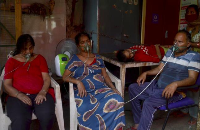 Không có giường bệnh, người mắc COVID-19 phải ngồi ngoài đường thở oxy