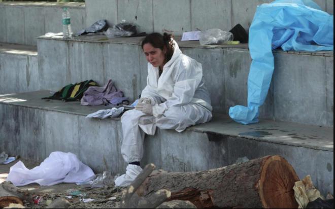 Một nhân viên y tế ngồi thẩn thờ khi xung quanh nhìn đâu cũng là người bệnh và người chết