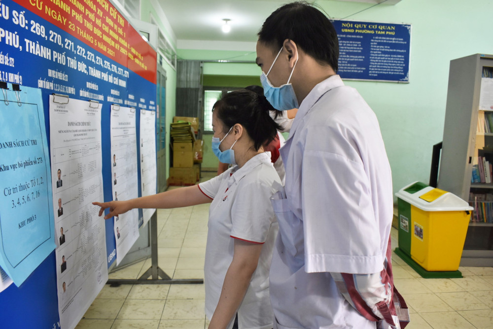 Cử tri theo dõi danh sách ứng cử viên được niêm yết tại UBND P.Tam Phú, TP.Thủ Đức, TP.HCM - Ảnh: hải liên