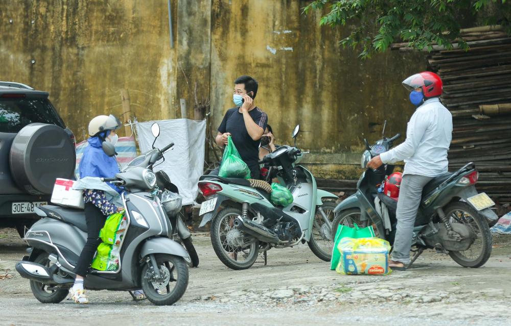 Rất nhiều người nhà của các bệnh nhân mang đồ ăn cùng nhu yếu phẩm đợi bên ngoài khu vực cách ly để đưa vào trong cho người thân.