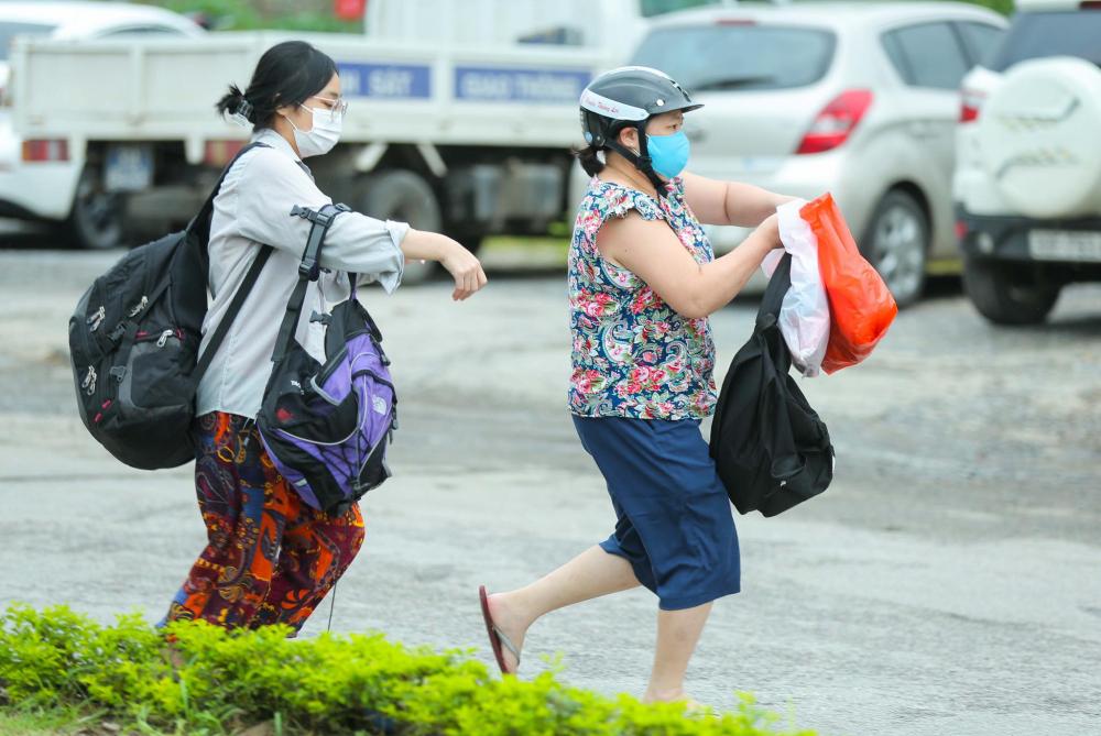 Người dân hối hả mang nhu yếu phẩm cần thiết đến bệnh viện sau khi nghe tin phong tỏa