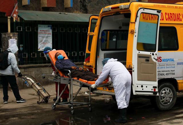 Bệnh nhân COVID-19 được chuyển từ xe cấp cứu tới bệnh viện khi làn sóng coronavirus lớn thứ hai dâng cao ở Kathmandu, Nepal