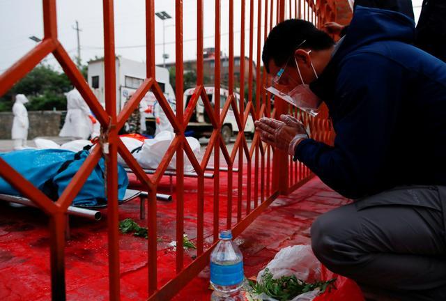 Một thành viên trong gia đình cầu nguyện cho nạn nhân của COVID-19 bên ngoài hàng rào ngôi đền Pashupatinath