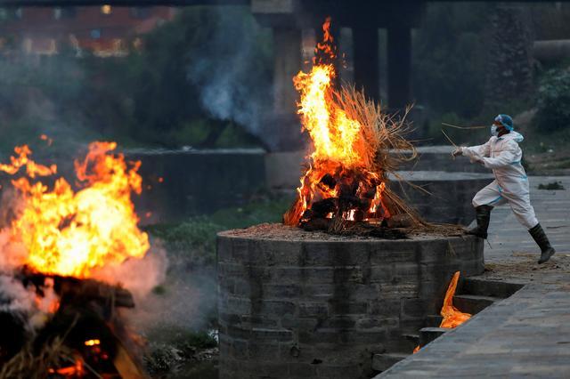 Một người đàn ông mặc thiết bị bảo vệ cá nhân (PPE) thiêu xác nạn nhân COVID-19 tại một lò hỏa táng ở Kathmandu hôm 3/5