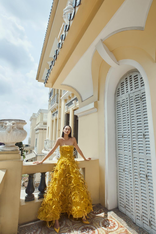 Chiếc váy màu vàng ấm áp được điểm xuyết bằng những chi tiết nơ đính nổi độc đáo. Trang phục có phom cổ điển nhưng trông ấn tượng nhờ cách xử lý tiểu tiết.
