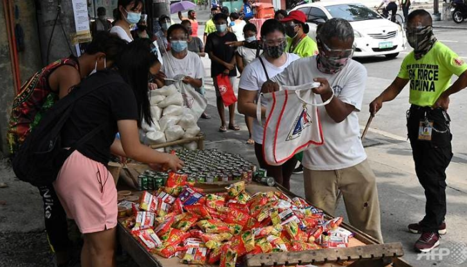 Người dân nhận lương thực miễn phí ở thành phố Quezon, ngoại ô Manila, Philippines - Ảnh: AFP