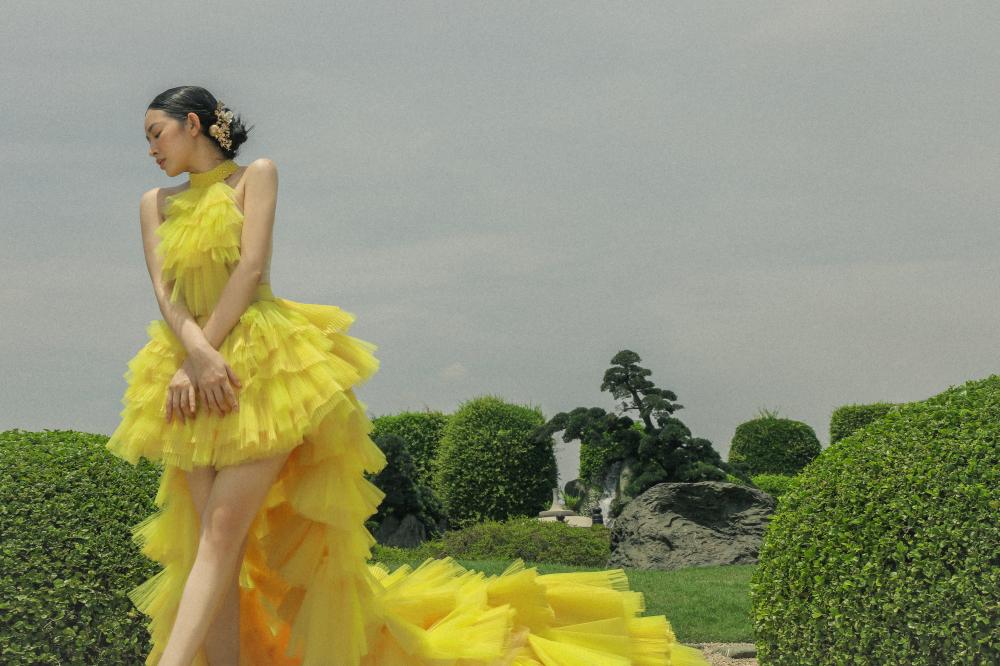 Trong chiếc đầm vàng cổ yếm, nhiều tầng của Tony Hoàng, Mai Thanh Hà tự tin khoe vóc dáng mảnh mai, đôi chân thon thả. Bộ trang phục thoạt trông khá cầu kỳ nhưng nữ diễn viên lại không ngần ngại đứng trên mỏm đá cao thể hiện thần thái của một nàng công chúa xinh đẹp, soi mình bên mặt hồ.