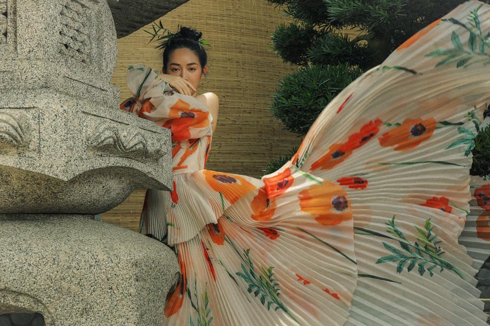 Trong khi đó, bộ đầm trễ vai, xếp ly với họa tiết là những bông hoa to của nhà thiết kế Từ Trung Hiếu thì tạo cảm giác bồng bềnh, nữ tính.