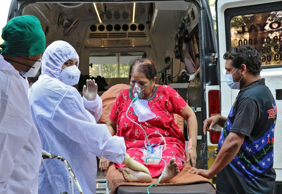 Nhân viên y tế và người thân bế một phụ nữ từ xe cấp cứu đến điều trị tại cơ sở chăm sóc bệnh nhân COVID-19 ở Mumbai
