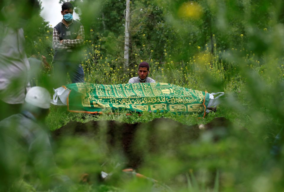 Thân nhân đứng cạnh thi thể của một người đàn ông đã chết vì COVID-19, khi họ chờ đợi một ngôi mộ được chuẩn bị ở ngoại ô Srinagar