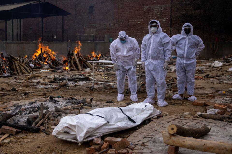 Những người đàn ông mặc đồ bảo hộ đứng cạnh thi thể của người thân đã chết vì COVID-19, trước khi hỏa táng cô ấy tại một khu hỏa táng ở New Delhi