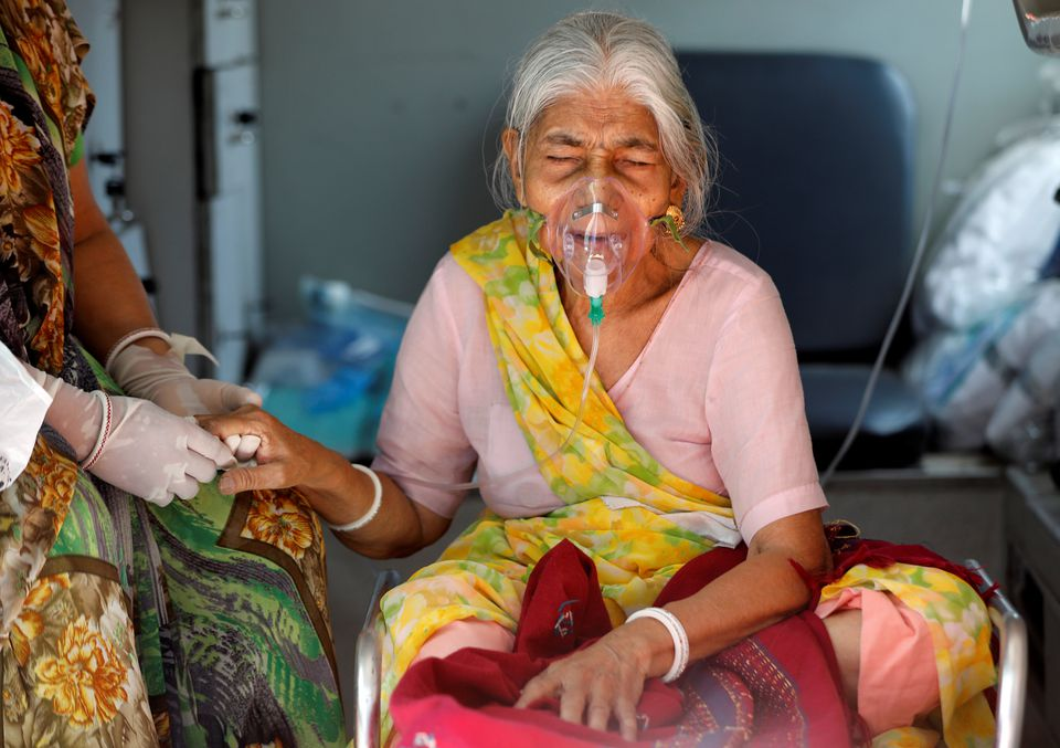 Lilaben Gautambhai Modi, 80 tuổi, đeo mặt nạ dưỡng khí, ngồi bên trong xe cấp cứu khi chờ đến lượt điều trị ở Ahmedabad
