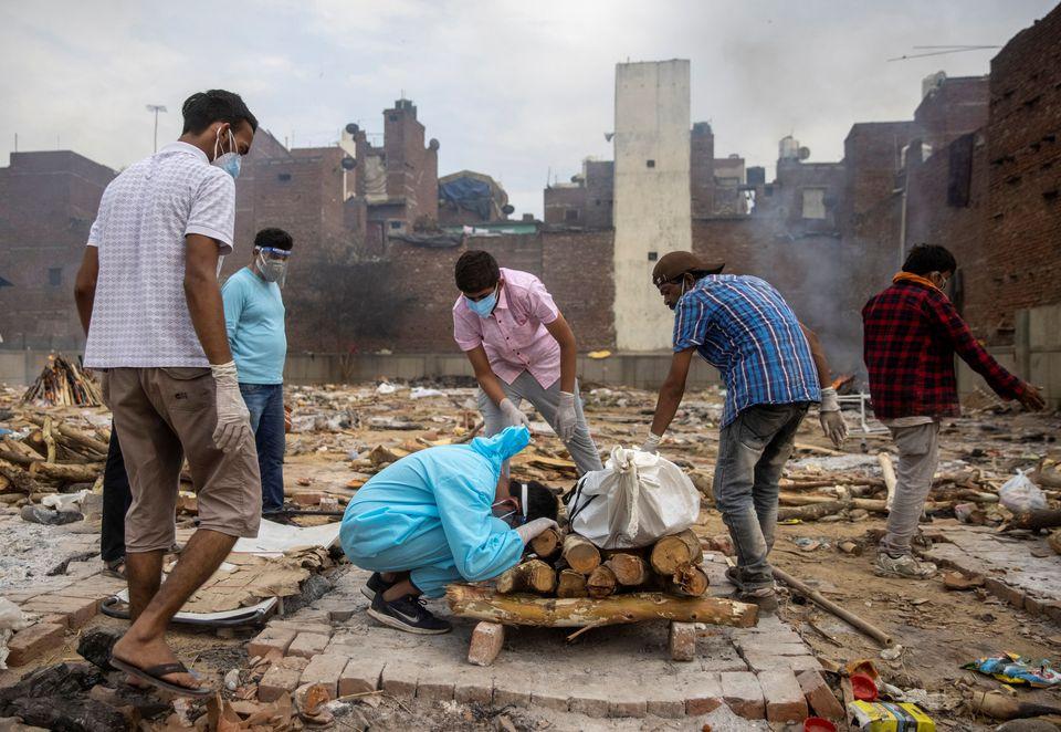 Pranav Mishra, 19 tuổi, gục khóc bên cạnh thi thể của mẹ mình Mamta Mishra, 45 tuổi, người đã chết vì bệnh coronavirus (COVID-19), trước khi hỏa táng tại một khu hỏa táng ở New Delhi
