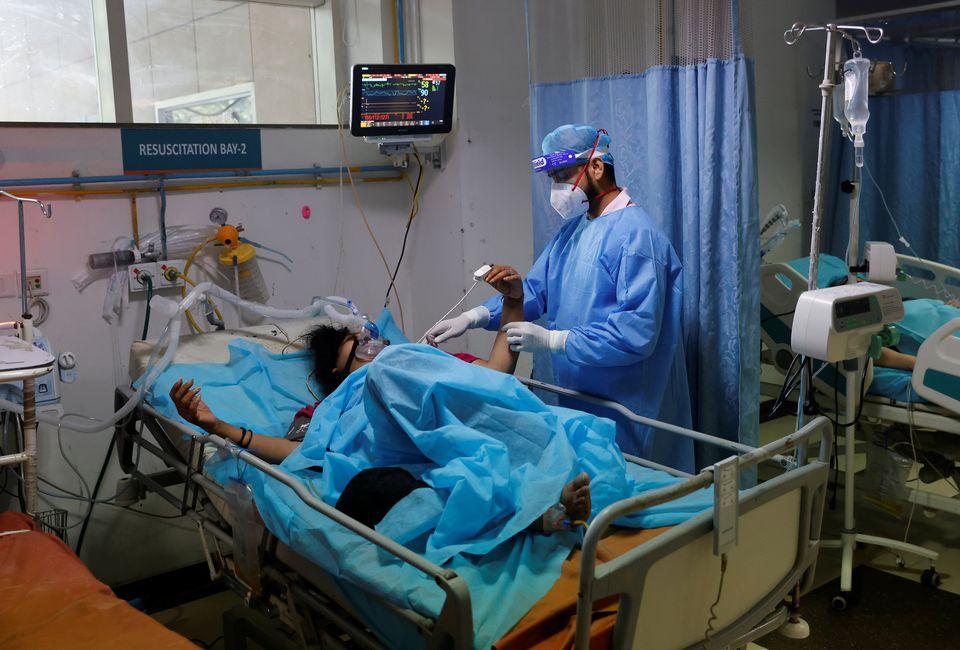Nhân viên y tế kiểm tra một bệnh nhân COVID-19 trong phòng cấp cứu của Bệnh viện Safdarjung ở New Delhi, Ấn Độ