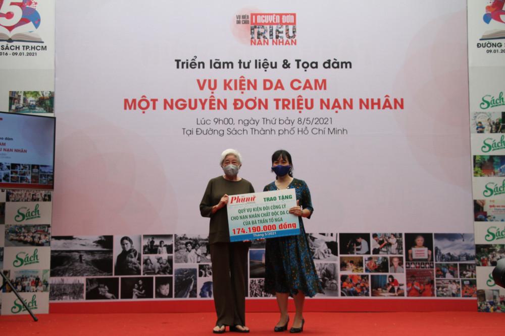 Bà Nguyễn Thụy Diễm Chi (bên phải) - Phó Trưởng Ban Chính trị - Xã Hội, đại diện cho Báo Phụ Nữ TPHCM trao bảng tượng trưng số tiền ủng hộ của bạn đọc Báo Phụ Nữ cho đại diện gia đình bà Trần Tố Nga.