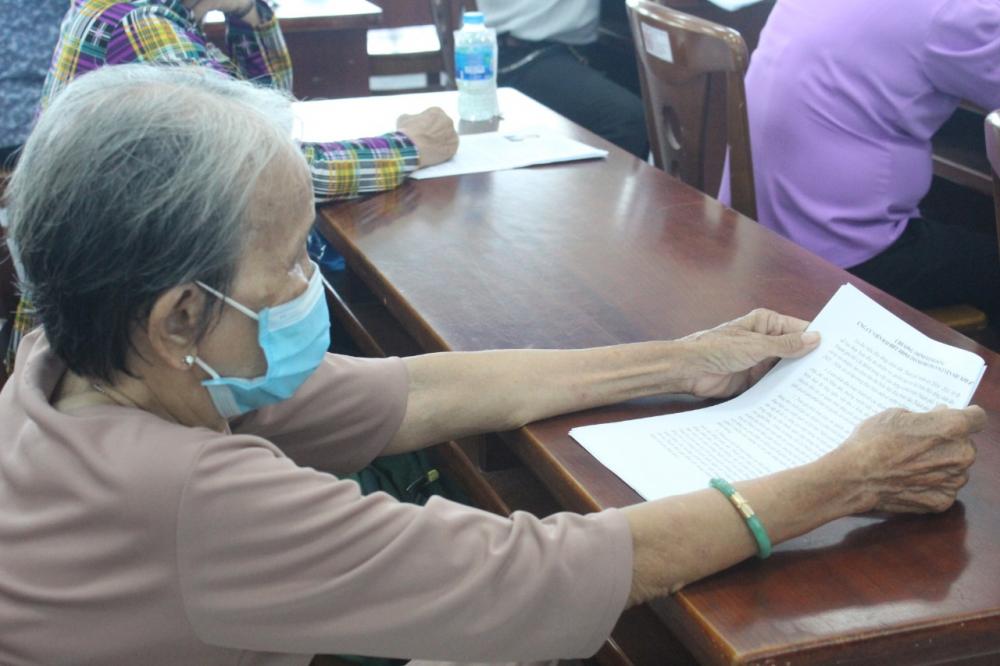 Một cử tri lớn tuổi nghiên cứu chương trình hành động của các ứng cử viên.