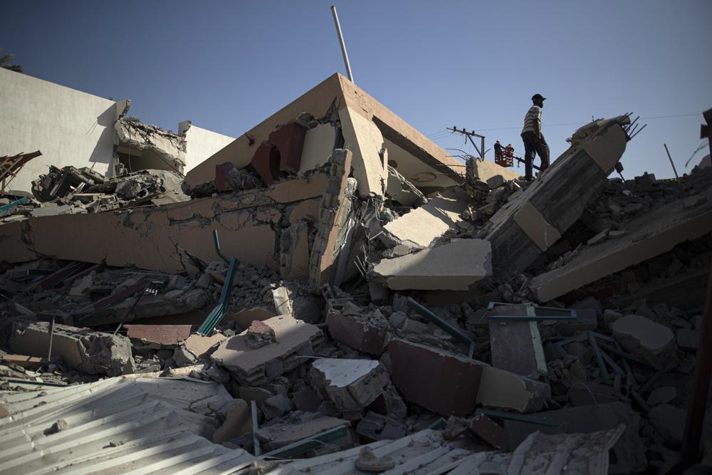 Công nhân Palestine sửa chữa các dây cáp điện bị hư hỏng sau cuộc không kích của Israel phá hủy một tòa nhà thuộc phong trào Hamas