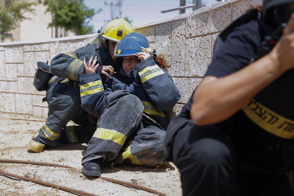 Các nhân viên cứu hỏa Israel ẩn nấp khi tiếng còi báo động vang lên cảnh báo về các tên lửa từ dải Gaza, ở thị trấn Ashkelon, miền nam Israel