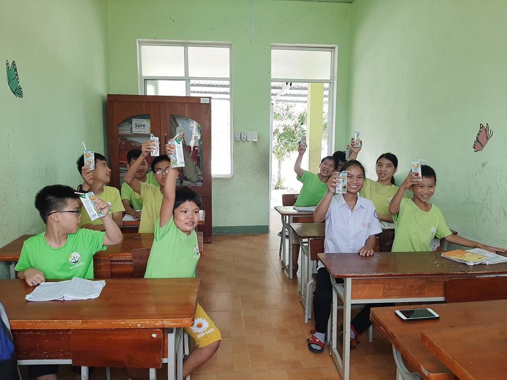 Trẻ em vui mừng khi được nhận sữa từ chương trình Quỹ sữa Vươn cao Việt Nam năm 2021. Ảnh: Vinamilk