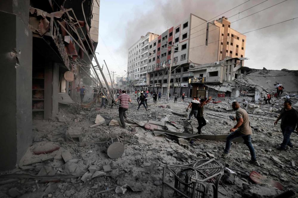 Người dân Palestine kiểm tra thiệt hại giữa đống đổ nát trước tòa tháp Al-Sharouk, sau khi tòa nhà sụp đổ vì bị tấn công bởi cuộc không kích từ Israel