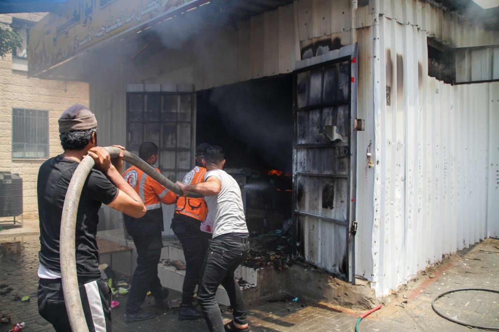 Các thành viên của lực lượng phòng vệ dân sự Palestine dập tắt ngọn lửa tại một tòa tháp dân cư ở Beit Lahia, phía bắc Dải Gaza, sau khi nó bị trúng tên lửa của Israel