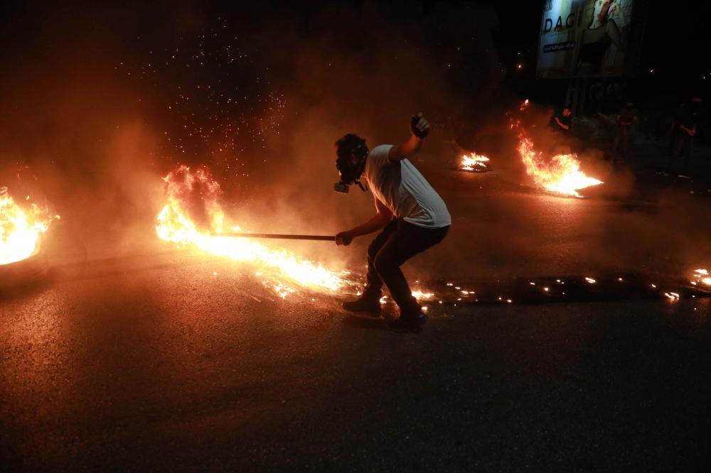 Một người biểu tình Palestine đốt lốp xe để đáp trả lực lượng an ninh Israel tại trạm kiểm soát Beit El