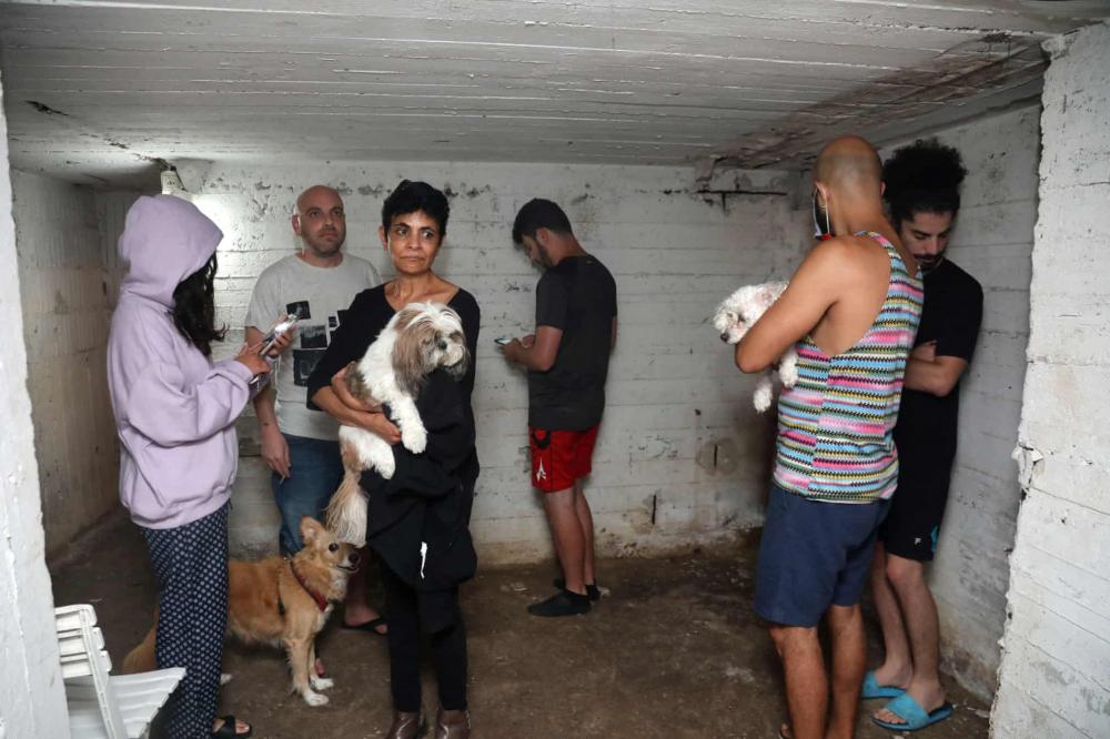 Người dân trú ẩn trong tầng hầm của một tòa nhà ở thành phố Tel Aviv của Israel khi còi báo động kêu lên, cảnh báo tên lửa được phóng từ Dải Gaza