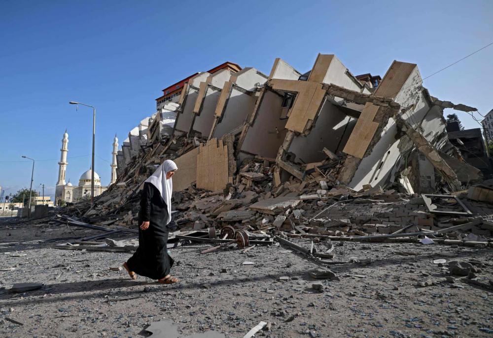 Một phụ nữ Palestine đi ngang qua tòa nhà bị phá hủy ở thành phố Gaza.