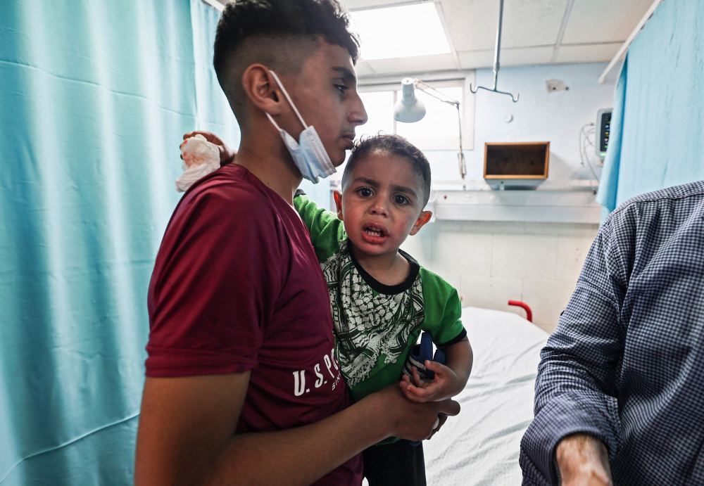Một thanh niên Palestine an ủi một cậu bé bị thương đang được chăm sóc y tế tại bệnh viện al-Shifa sau cuộc không kích của Israel ở Gaza