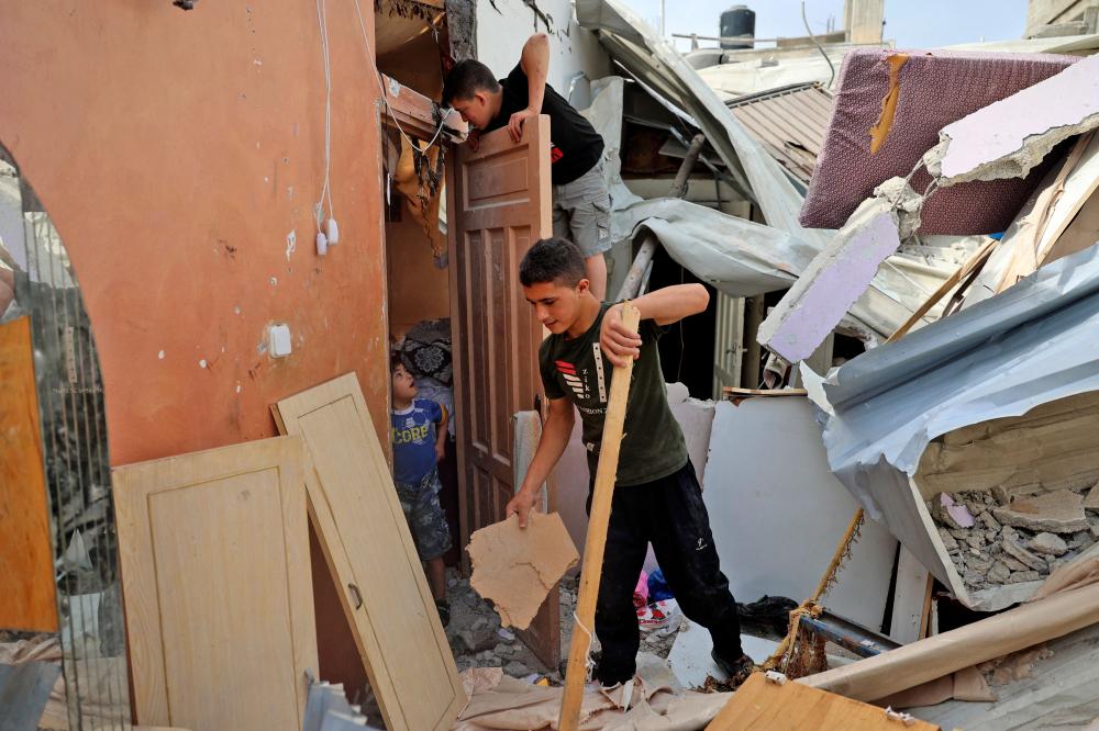 Trẻ em Palestine kiểm tra ngôi nhà bị hư hại sau cuộc không kích của Israel tại Trại tị nạn Al-Shati ở thành phố Gaza
