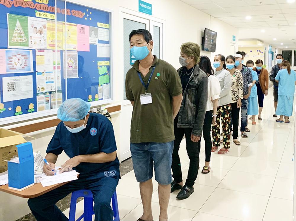 Thân nhân, bệnh nhân tại Bệnh viện Hùng Vương xếp hàng khai báo y tế và chờ lấy mẫu xét nghiệm - Ảnh: Phạm An