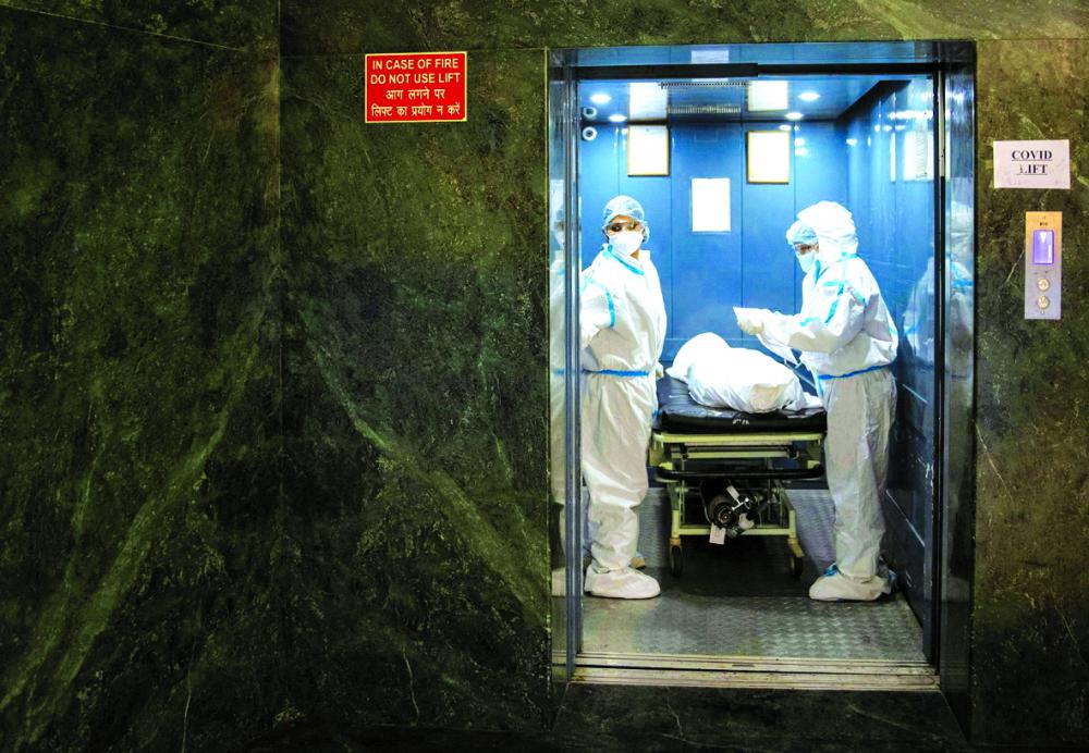 Nhân viên bệnh viện vận chuyển thi thể của một người chết do biến chứng liên quan đến COVID-19, từ khu ICU tại Bệnh viện Holy Family ở New Delhi