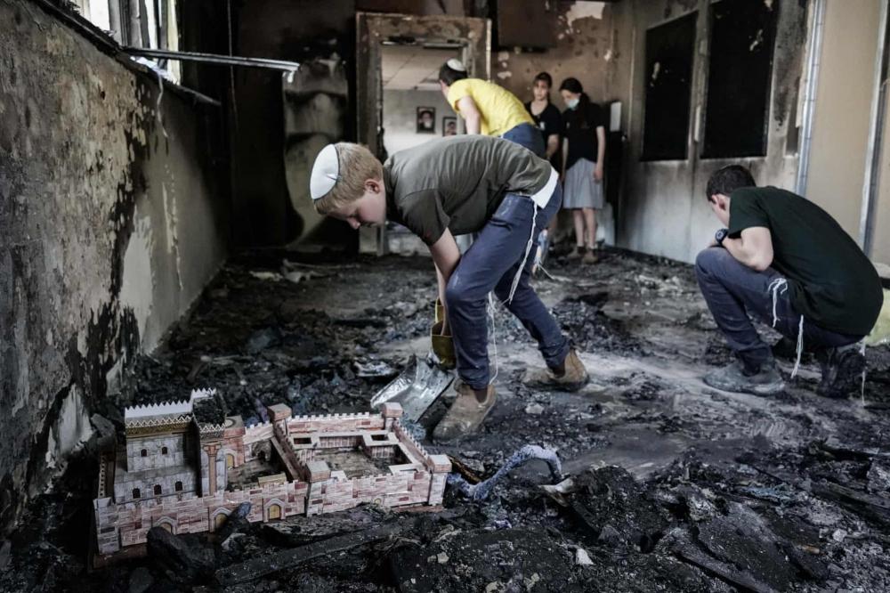 Người dân nhặt nhạnh các vật phẩm còn sót lại từ một giáo đường Do Thái bị đốt cháy ở Lod