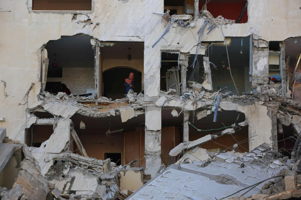 Người Palestine kiểm tra một tòa nhà bị hư hại trong cuộc không kích của Israel ở thành phố Gaza