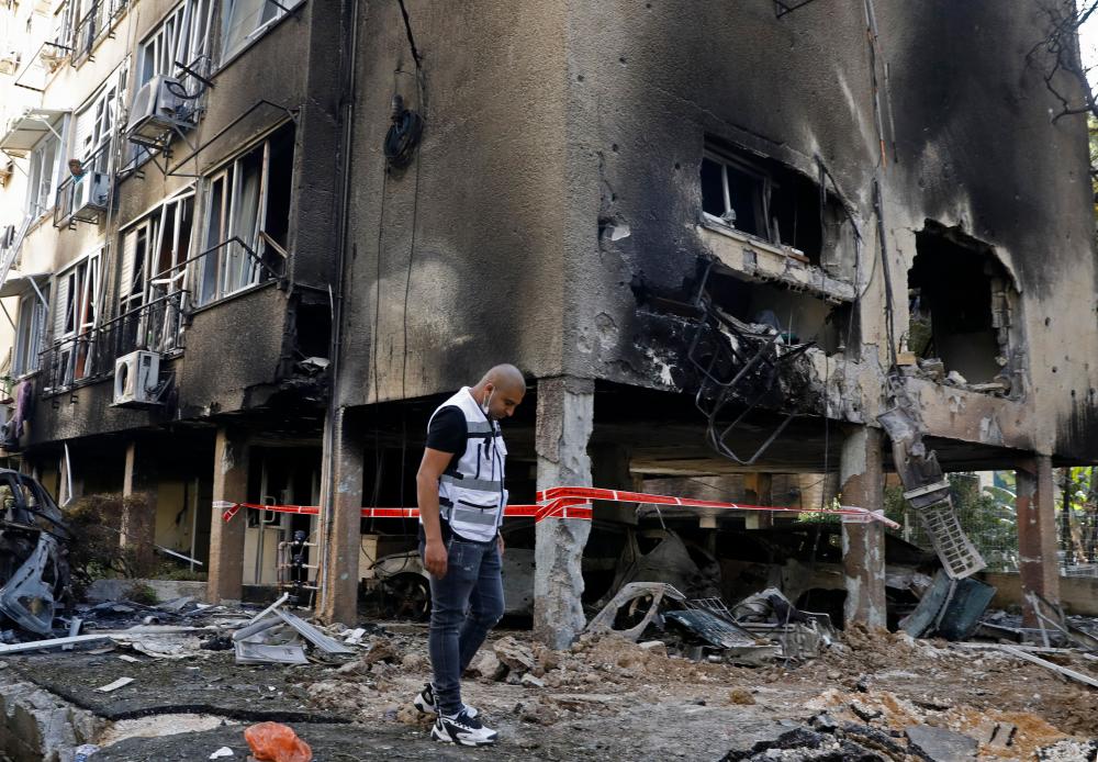 Một người đàn ông Israel ở thành phố Petah Tikva, miền trung Israel kiểm tra thiệt hại do tên lửa phóng từ dải Gaza do Hamas kiểm soát