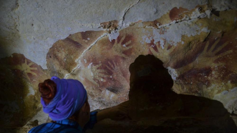 Những dấu tay trên vách hang động được tô đậm nhờ vào thứ bột đỏ