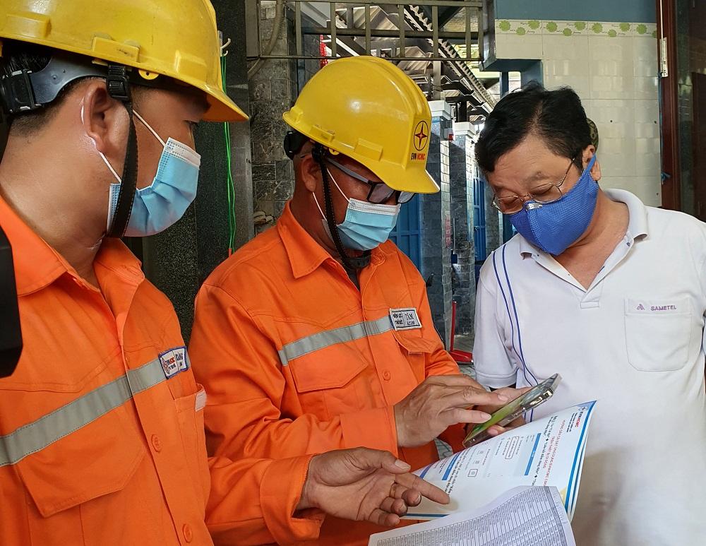 Nhân viên Công ty Điện lực Thủ Đức hướng dẫn người dân cài App EVNHCMC CSKH. Ảnh: EVNHCMC