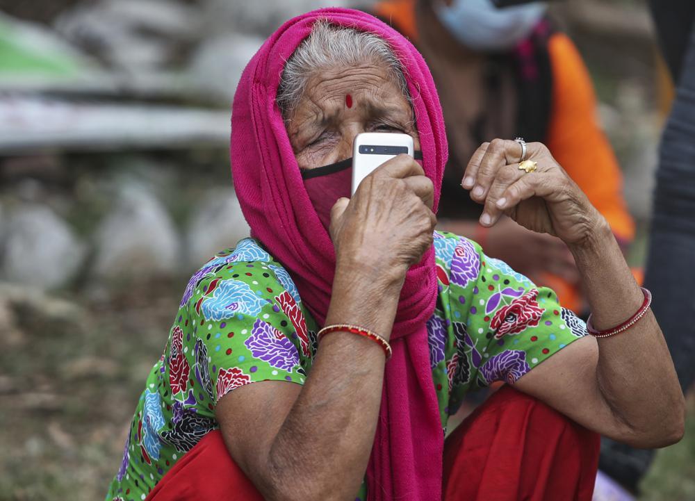 Một người phụ nữ đeo khẩu trang để đề phòng virus coronavirus nói chuyện trên điện thoại di động khi chờ được xét nghiệm COVID-19 ở Jammu